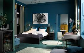 a medium sized bedroom furnished with a black brown bed for two combined with chest bedroom furniture at ikea
