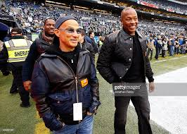 dr dre and music producer jimmy iovine on the field before the seattle seahawks take beats by dre office
