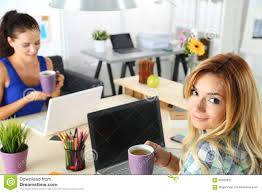 two female designers in office drinking morning tea stock photo two female designers in office drinking morning tea royalty stock photography