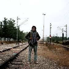 young refugees carry few belongings and many dreams proof portrait of a man standing in a hoodie a backpack in the middle of train