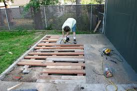 working creating patio: brooke working on unscrewing the plywood from the x framework below