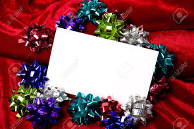 a blank notecard surronded by christmas decoration bows on a a blank notecard surronded by christmas decoration bows on a red background add copy or