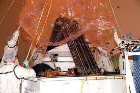 Workers lift the protective wrapping from <b>Genesis</b> a spacecraft ...