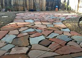 stone patio installation: flagstone patio singles of several colors combined to create this backyard patio pathway