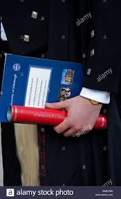 detail of male hand holding degree scroll in tube after graduating detail of male hand holding degree scroll in tube after graduating at edinburgh university scotland uk europe