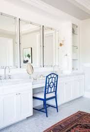 bathroom features gray shaker vanity: white and gray bathroom features a white shaker vanity topped with carrera marble under a studded mirror illuminated by a glass and brass wall sconce