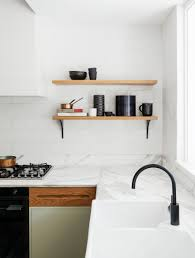 country kitchen column spout: above meet the curvaceous kitchen the calacatta marble counters are detailed with rounded edges that are echoed by the oak finger grooves on the cabinets