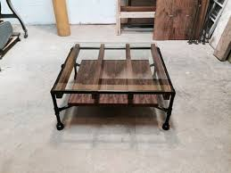 a modern industrial coffee table made of black steel pipe walnut wood slats and black steel pipe furniture