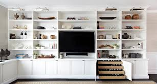 chic living room features a wall of floor to ceiling built in shelves and cabinets surrounding a flat panel tv next to a cabinet fitted with pull out wine built living room