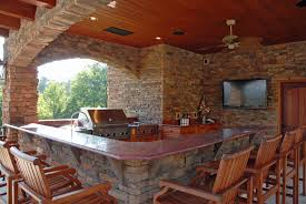 patio outdoor stone kitchen bar: outdoor kitchen designs with bar concept and wooden chairs