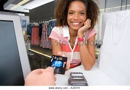clothes shop assistant store stock photos  amp  clothes shop assistant    young w  by counter in clothes shop  smiling  portrait  shop assistant holding out