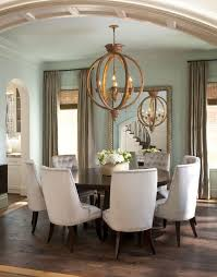 dining room table mirror top: plush dining chairs contrast with dark wood circular dining table a large gilded mirror