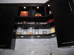 dark cabinets and bright led under cabinet lighting in the kitchen with grey backsplash cabinet lighting modern kitchen