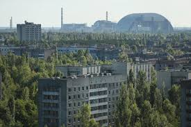 new safe confinement in chernobyl the saturday paper the forested ruins of the exclusion zone surrounding the chernobyl plant and the huge arch of the nsc during construction