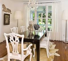 eclectic dining room with cowhide rug glossy black lacquer dining table hollywood regency white chippendale dining chairs and white sheers black lacquer dining room