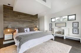 large bedroom with big white bed and gray wooden wall panel also white wall and ceiling captivating white bedroom