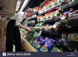 store clerk in a large supermarket organizes packaged produce stock photo store clerk in a large supermarket organizes packaged produce salads on shelves for