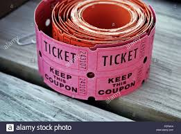 close up of a roll of pink raffle tickets on wood stock photo close up of a roll of pink raffle tickets on wood