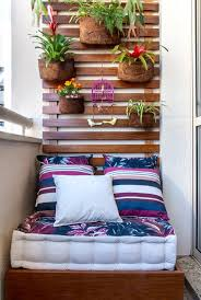 contemporary small patio ideas with beautiful leaf pattern mattress includes cute pillows under growing garden flower attached on wooden wall decor terrific small balcony furniture ideas fashionable product