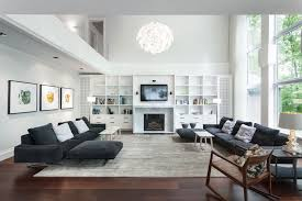 cream couch living room ideas: round hang lamp large modern living room with black sofas on the white rug on the