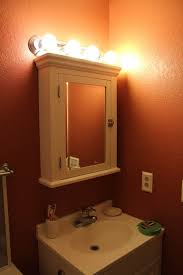 furniture attractive bathroom lighting for medicine cabinets using bulb wall sconce over mirrored swing doors with attractive vanity lighting bathroom lighting