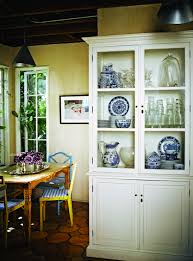rustic hutch dining room: eclectic dining room with white hutch sheet metal cone pendants designed by jacqui getty rustic dining table yellow dining chairs with blue gingham