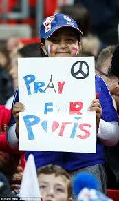 a young fan holds a banner in support of the victims of the paris atrocities ben office fan