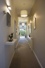 hallway lighting ideas with white drum shade pendant lamps and wall sconces over framed wall best hallway lighting