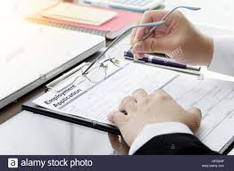 businessman or hr manager review a blank employment application businessman or hr manager review a blank employment application form magnifier and computer laptop