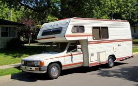 how to choose the right rv to live in for full time travelers photo via older brown and orange striped camper on a toyota truck chassis