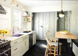 brass sconces and hardware in kitchen with black floor black glass globe pendant