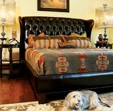 black leather upholstered bed with tufted headboard and brown wooden short legs in cream western bedroom brown leather bedroom furniture