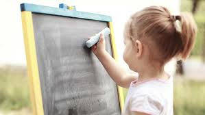 tips on how to help young children learn to write young girl writing on a chalkboard a piece of chalk