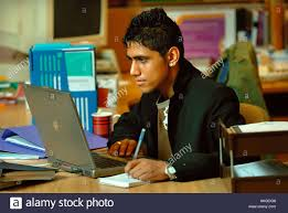 a teenage boy working on a laptop computer in an office a teenage boy working on a laptop computer in an office environment uk