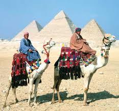 Photograph Men ride camels near the three pyramids of Giza in Egypt  Kids Britannica