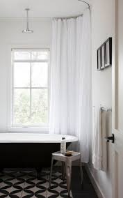 reglazing tile certified green: guest bathroom with a black tub and black and white tiles