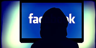 your facebook profile can tell your boss how well you work the shadowy w looking at facebook on computer screen