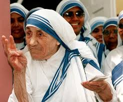 Mother Teresa talks to nuns from the Missionaries of Charity after a mass at the congregation