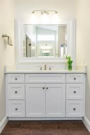 bathroom features gray shaker vanity: white shaker cabinets pair with crisp quartz countertops and a white mirror for a clean fresh design in this timeless bathroom wood look tile floors lend