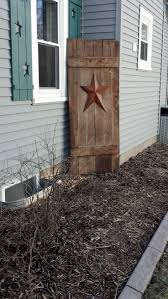metal star wall decor: old barn door turned decor could be used to hid unsightly tanks pipes and corners