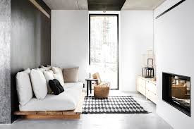 floor sitting furniture. modern neutral sitting room wood sofa with white cushions concrete floor and walls black furniture