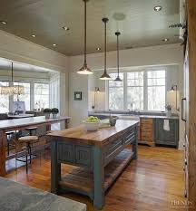 rustic kitchen island: like this island look for the kitchen moving cart the cabinets in this kitchen are pecky cypress amp were custom built by john zook the painted cabinets are