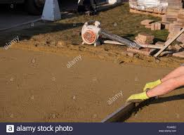 manual worker laying a sand screed base on a drive construction stock photo manual worker laying a sand screed base on a drive construction job in readiness for the laying of block paving manual worker