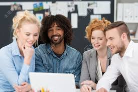 young business team working together sitting grouped around a stock photo young business team working together sitting grouped around a smiling african american colleague in a casual denim shirt as they work on a