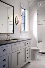 bathroom features gray shaker vanity: beautiful bathroom features full height subway tile backsplash framing a gray vanity sink topped with jet