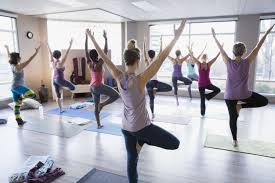 definition of a non traditional student women practicing tree pose in yoga class