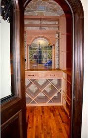 doorway of wine room showing wine barrel flooring and wood racking barrel wine cellar designs