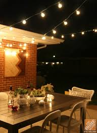a patio with outdoor string lights is the perfect spot for a romantic night in backyard string lighting