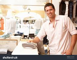 male s assistant checkout clothing store stock photo  male s assistant at checkout of clothing store