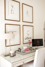 elegant home office with sketches in gold frames over white desk with silver nailhead trim topped art for home office